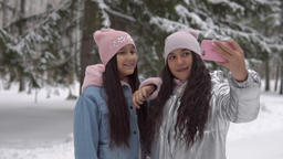 Two girlfriends with a good mood make selfie using a smartphone while standing Footage