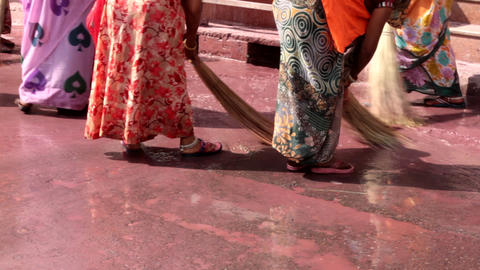 Indian women wash pavement in front of temple with brooms Footage