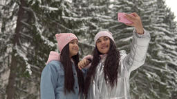 Two girlfriends make selfie on the background of the winter forest using a Footage