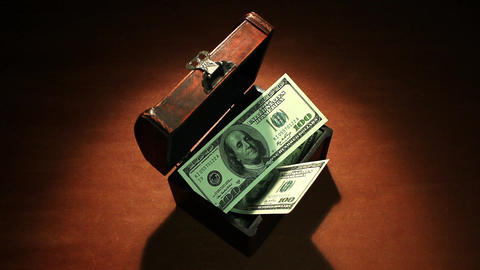Illegal enrichment (corruption). Money falls into an old chest. 100 dollars GIF