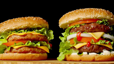 The concept of American fast food. Juicy American burger with two beef cutlets Footage