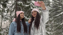 Two young girlfriends in winter clothes make selfie against the background of Footage