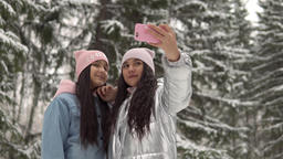 Two young girlfriends in winter clothes taking selfie against the background of Footage