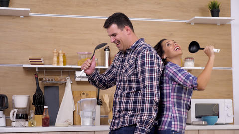 Happy positive couple in the kitchen singing Live Action