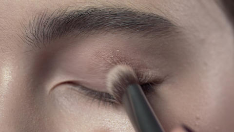 Macro shot of applying makeup to the woman's eyelid, evening makeup, smokey eyes Archivo