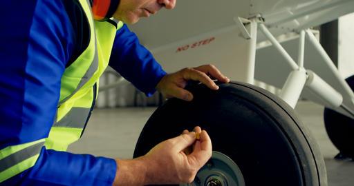 Engineer reparing aircraft wheel Live Action