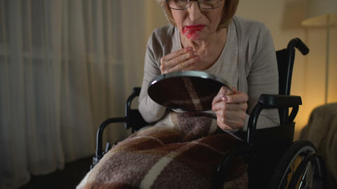 Depressed old lady smearing lipstick all over the face, crying for lost youth Live Action