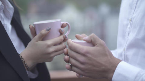 Male and female hands hold cups of coffe in their hands outdoors closeup Male Live Action