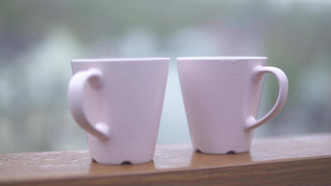 Two white coffee cups in the open air Focus moves from cups to the background Live Action