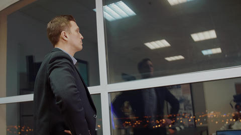 Back view of male entrepreneur dressed in corporate suit looking out of window Footage