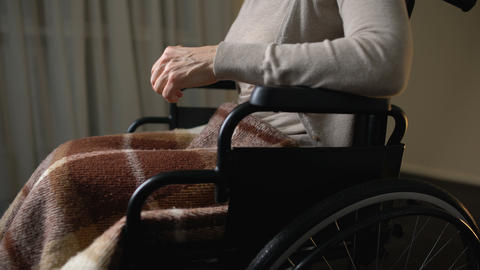 Invalid woman moving in wheelchair at home for elderly, charity foundations Live Action