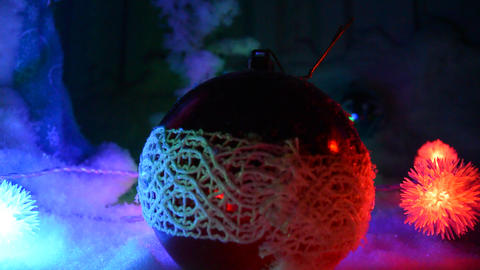 Christmas ball lying on the snow and flashing garland Live Action