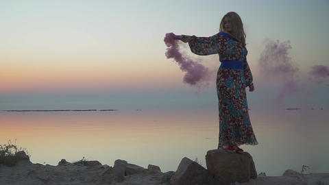 Lovely girl holding a pink smoke bomb Woman is standing on the rock Lovely girl Live Action