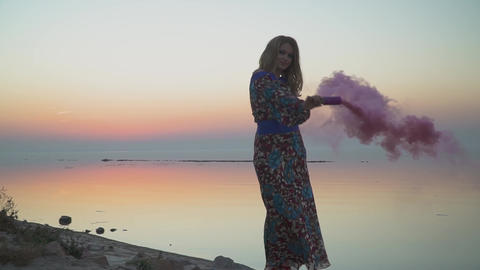 Lovely girl holding a pink smoke bomb Woman is standing... Stock Video Footage
