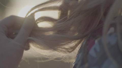 Female hand straightens hair close up Girl has blond hair S-log, ungraded Footage