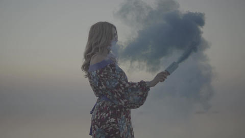 Cute woman holding a pink smoke bomb outdoors Lovely girl in a summer dress with ビデオ