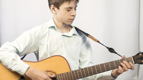 Teenager plays an acoustic guitar. Against the background of the light wall ビデオ