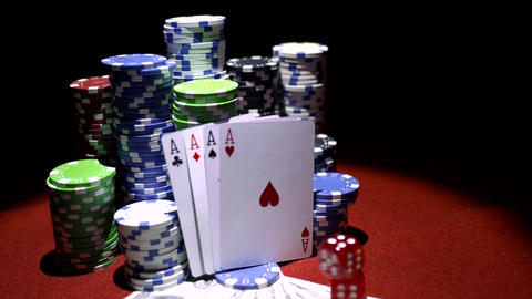 Four aces and poker chips with dollars and red dices on red table Footage