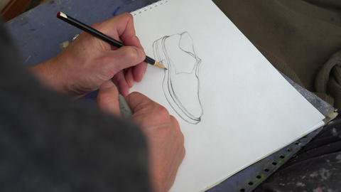 Professional illustrator and graphic artist draws a shoe Live Action