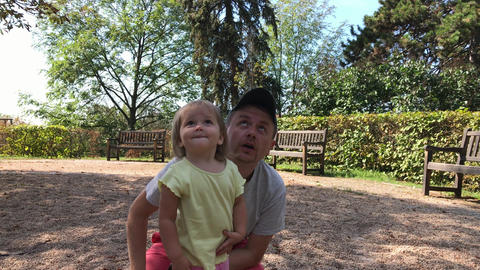 Father and little daughter look to sky in summer park Footage