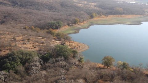 Drying up lakes and dry hills with arid wood and shrub vegetation in India Live Action