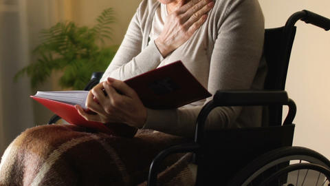 Woman in wheelchair looking at photo album, remembering happy youth moments Live Action