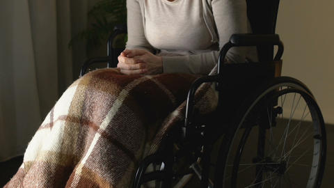 Lady in wheelchair rubbing hands, old age loneliness, abandoned in nursing home Footage