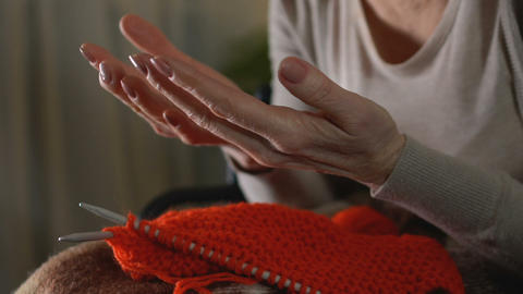 Sick old woman looking at shaking hands, unable to knit, old age difficulties Footage