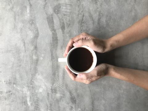 woman holding a white cup of hot coffee with her both hands on cement board フォト