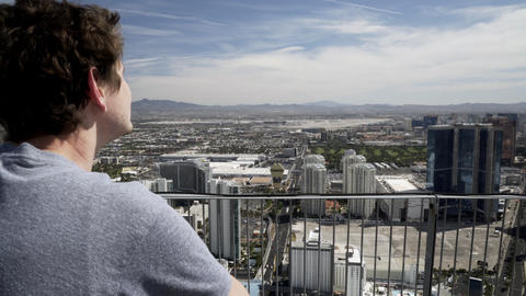 man looking over the guard railing of the stratosphere hotel in las vegas 4k Live Action