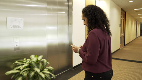 Businesswoman In A Modern Office Building Texting And Waiting For An Elevator 4k stock footage