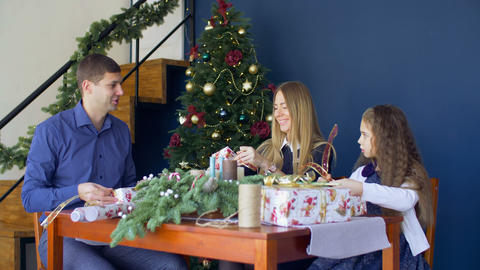 Cheerful famiy wrapping Christmas gifts at home Footage