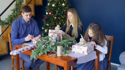 Family signing christmas gift boxes on xmas eve Footage