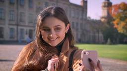 Cute smiling caucasian girl is taking selfies with cheerful smile and holding Footage