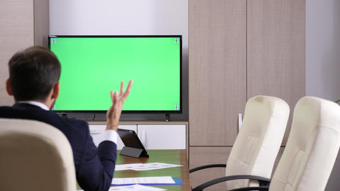 Back of businessman head talking to a green screen TV Footage