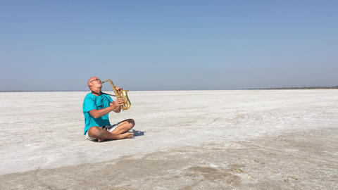 The saxophonist sits in the lotus position and plays the saxophone on the ビデオ