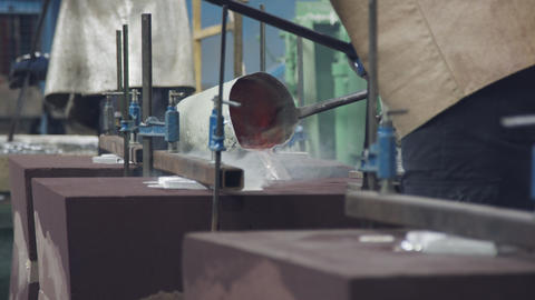Workers in a foundry pouring liquid Aluminum to a sand cast GIF