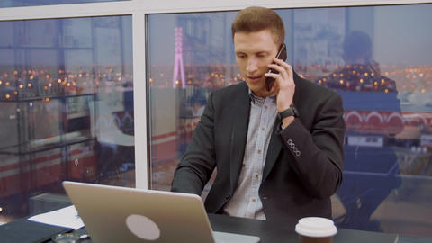 Handsome business man calling by mobile phone on workplace in business office Footage
