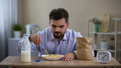 Single young man eating flakes milk with disgust in morning, bachelor nutrition Live Action