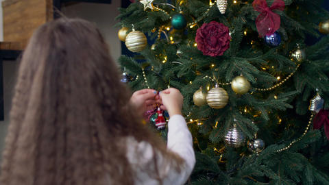 Child decorating Christmas tree with toys Footage