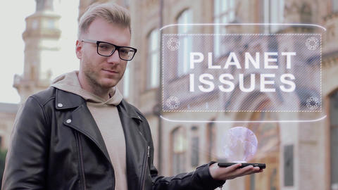 Smart young man with glasses shows a conceptual hologram Planet issues Footage