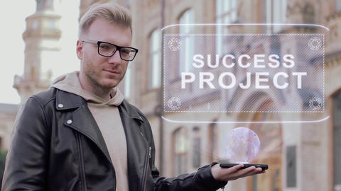 Smart young man with glasses shows a conceptual hologram Success project Footage
