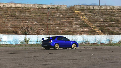 Blue automobile drifting on road, maneuvering during auto racing competition Live Action