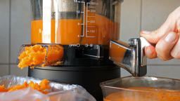 Slow juicer is making fresh carrot and orange juice Live Action
