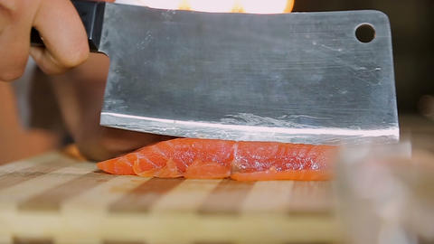 Lady cook hands slicing red fish on table, delicious appetizer, Asian cuisine Footage