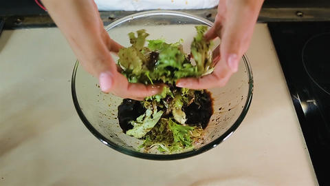 Woman chef combining lettuce salad with balsamic vinegar, mediterranean diet Live Action