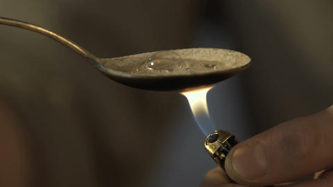 Man preparing heroin dose in spoon with lighter, drugs…, Live Action