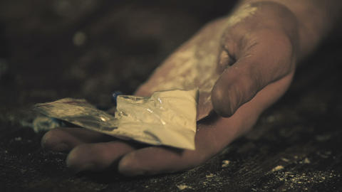 Hand with cocaine powder package falling down on floor, illegal drug trafficking Live Action