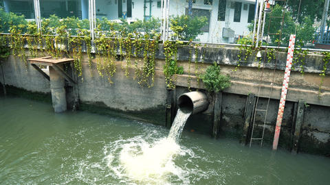 Dirty water flows through the drain pipe into the canal, low water level Footage