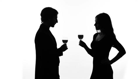 Silhouette of young couple drinking wine, getting acquainted, woman flirting Live Action